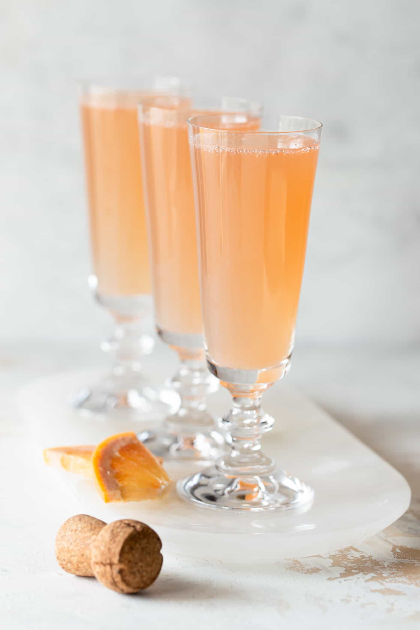 3 mimosas on a white tray with a white background and fresh grapefruit chunks for garnish.