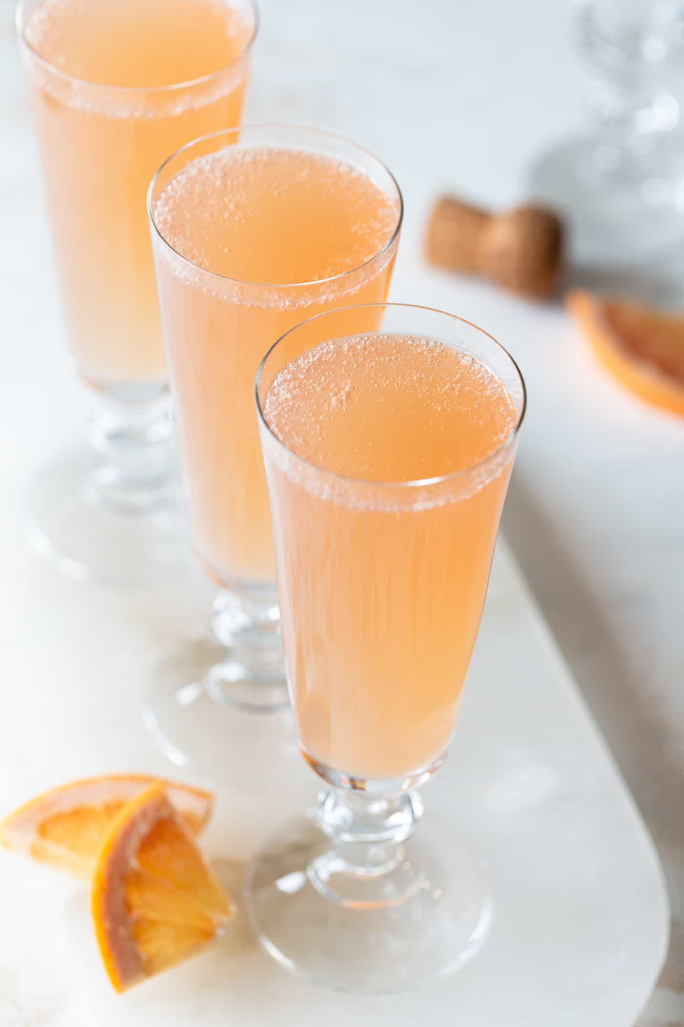 Top view of grapefruit mimosas on a white tray with fresh grapefruit wedges for garnish on a white background.
