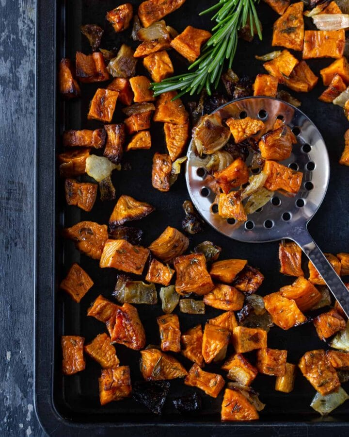 Dark sheet pan filled with rosemary roasted sweet potatoes and onions