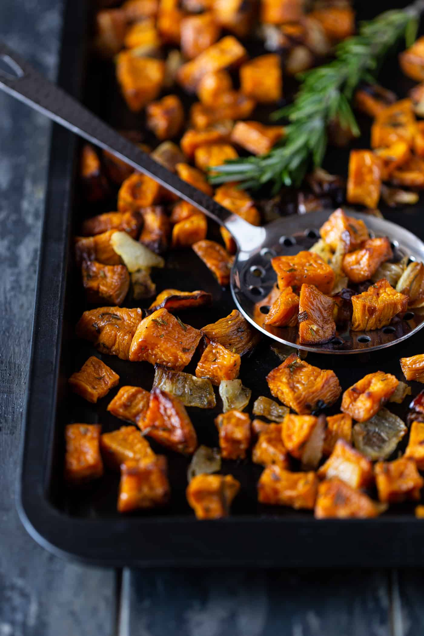 Dark sheet pan filled with rosemary roasted sweet potatoes and onions. garnished with fresh rosemary and a silver serving spoon.