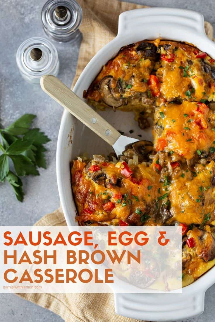 Pinterest image of Cheesy Sausage Hash Brown Egg Casserole in a white oval baking dish with fresh parsley for garnish.
