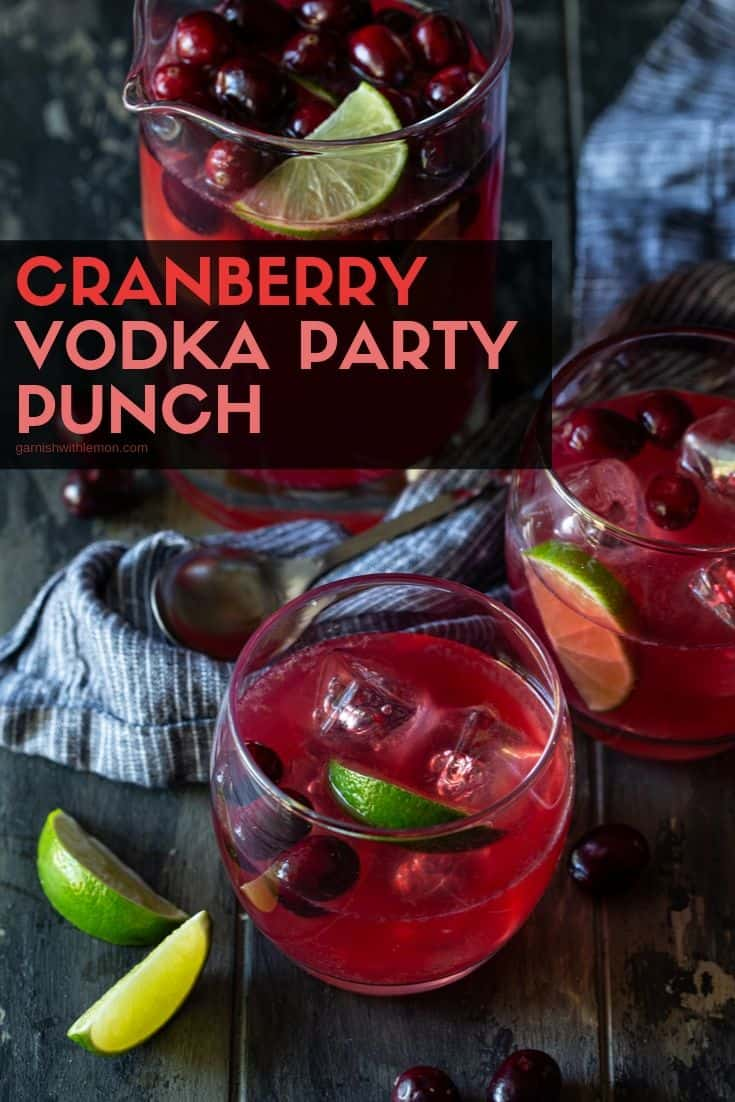 Fresh lime wedges and fresh cranberries floating in low ball glasses and a pitcher that are filled with Cranberry Vodka Punch.