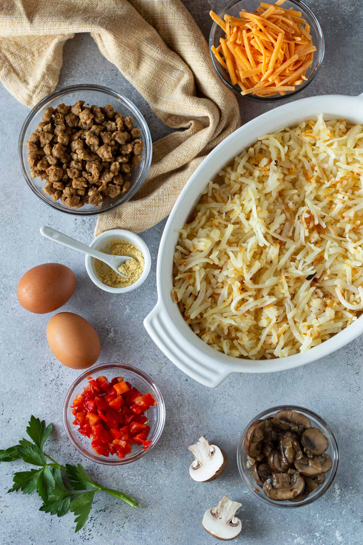 Ingredients needed for sausage hash brown and egg casserole in bowls on a white surface.