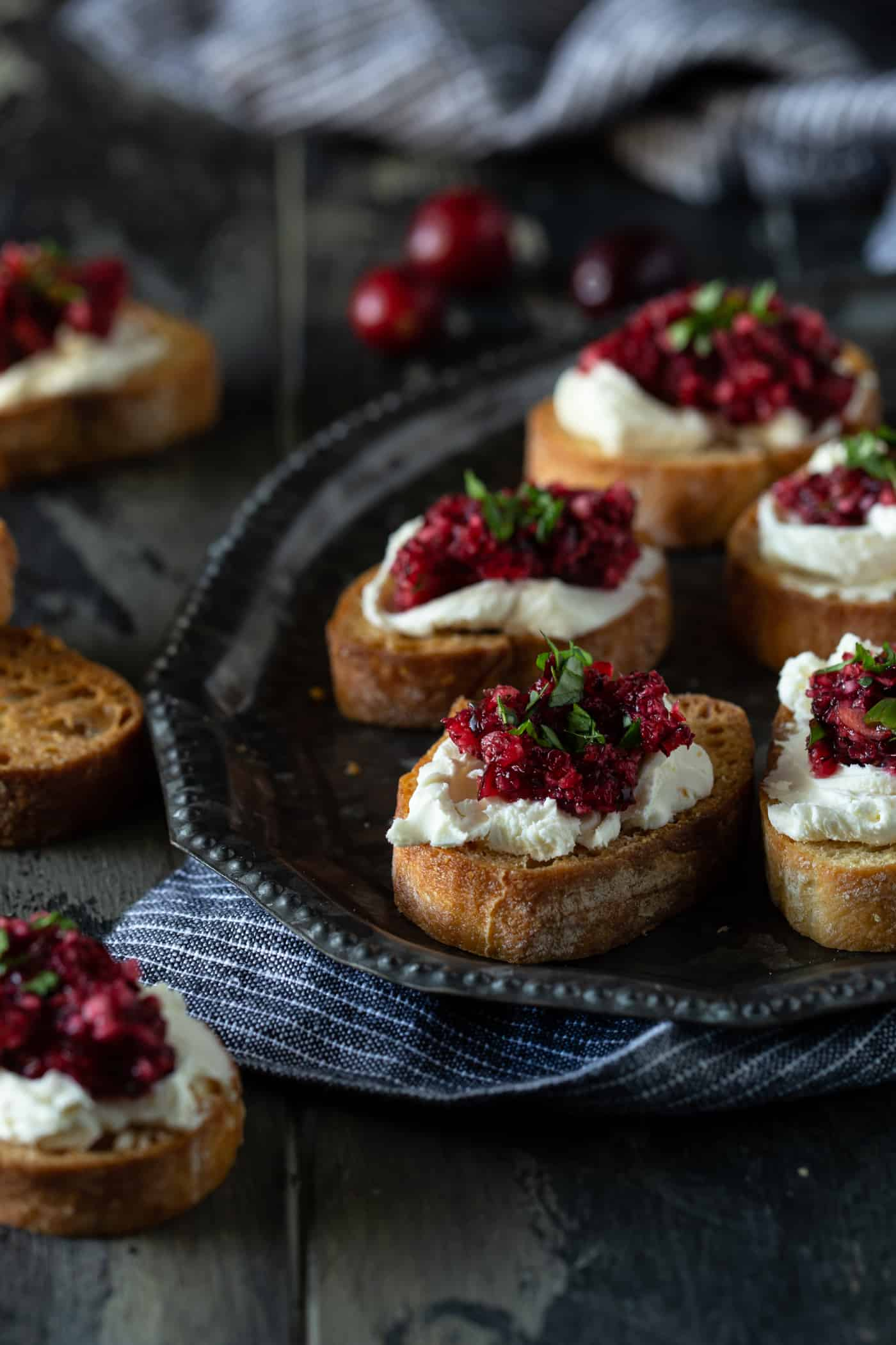 A plate of food with crostini on a table, with Cheese and Cranberry.