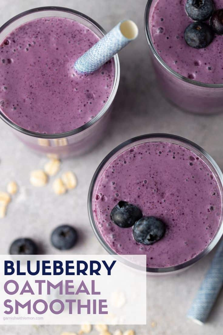 purple smoothies in glasses with straws and oats.