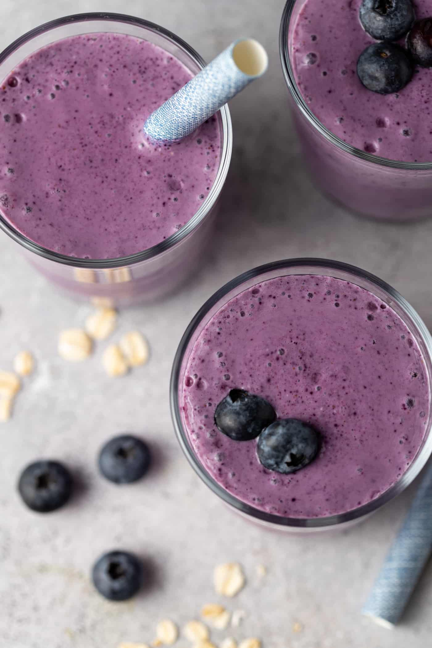 top down image of purple smoothies in glasses with fresh blueberries.
