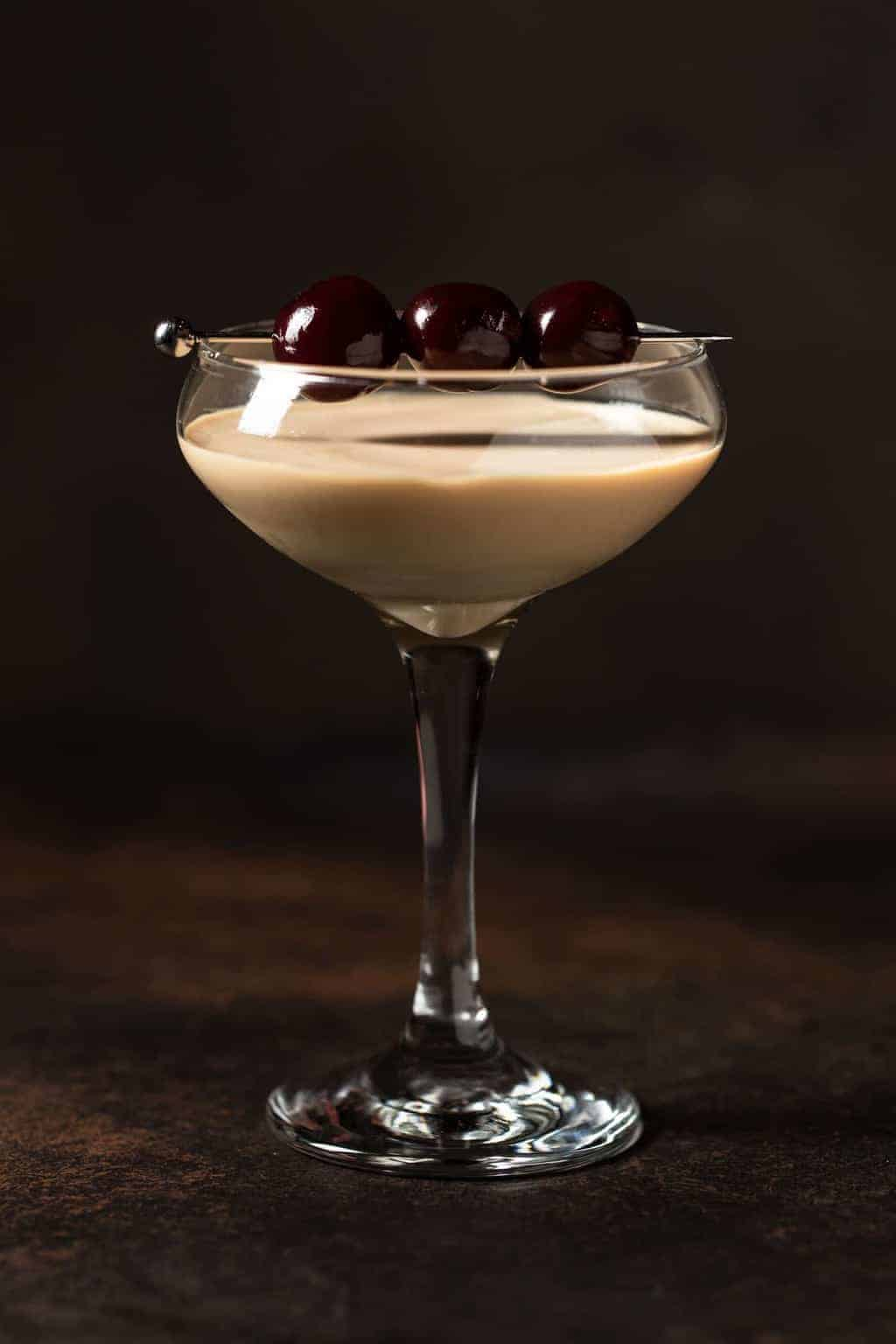 Single Cherry Chocolate Martini in a coupe glass with Luxardo cherries skewered on top.