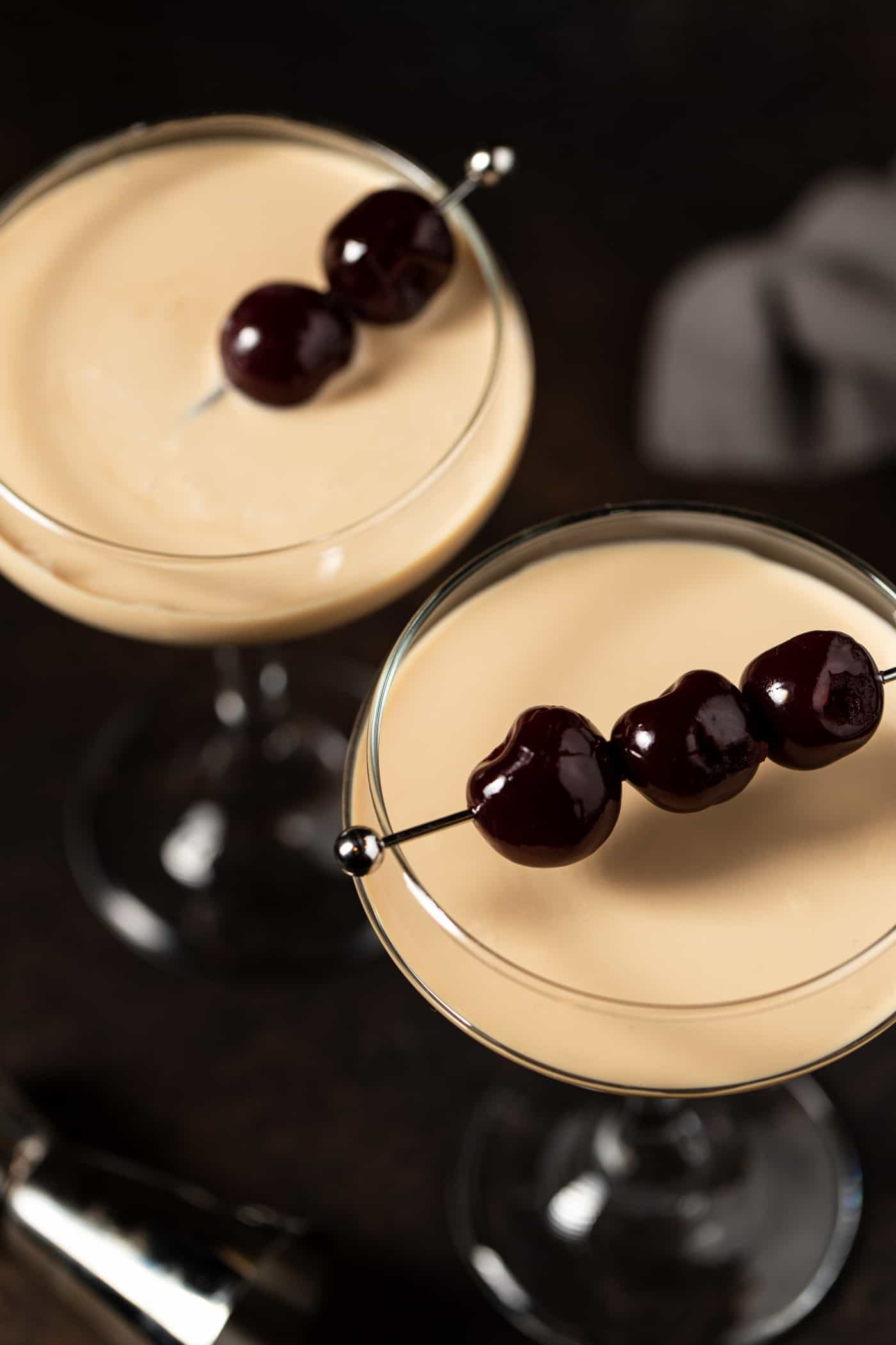 Top down image of dessert martinis garnished with luxardo cherries.