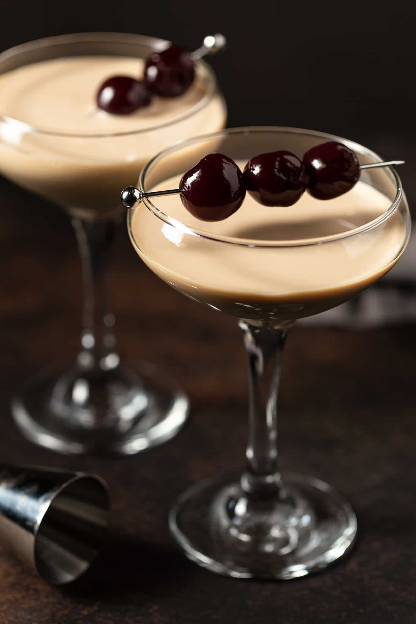 ¾ angle of luxardo cherries on a skewer garnishing a chocolate covered cherry martini.