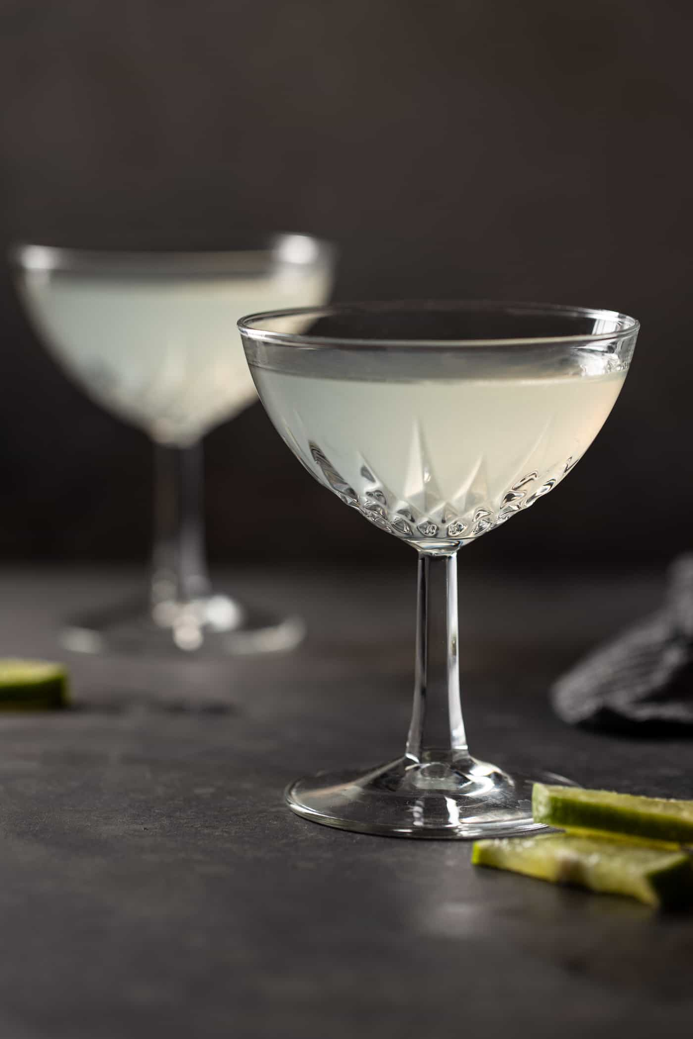 Two coupe glasses filled with Elderflower Gin Gimlet Cocktails on a dark wood board.