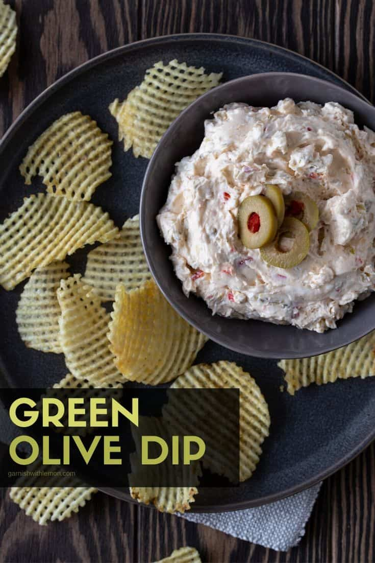 Close up of olive dip in bowl with chips.