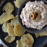 Green olive dip on a plate, with sliced olives and chips.
