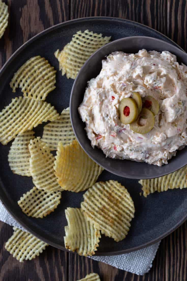 top down picture of dip in a dark gray bowl with sliced green olives on top and ridged potato chips for dipping.