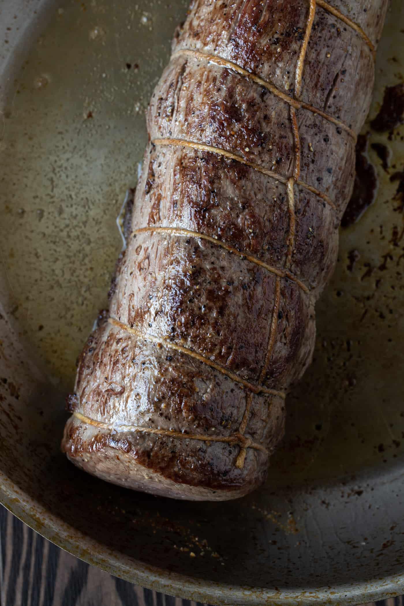 Uncut roasted beef tenderloin in skillet.