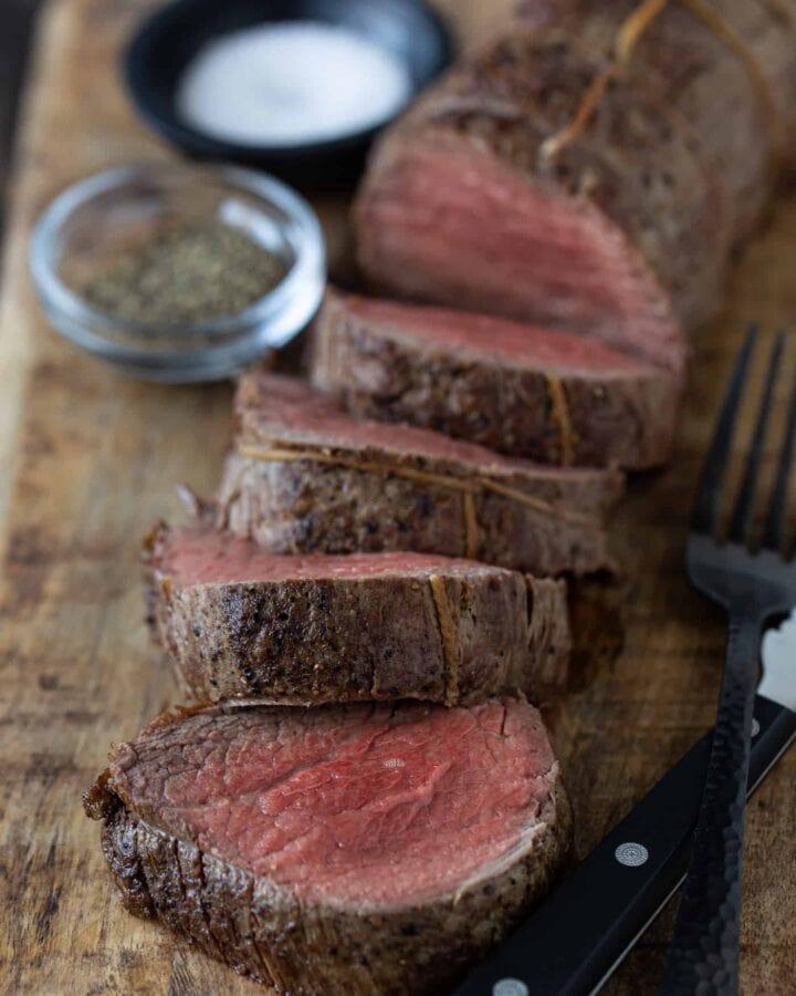 Sliced beef tenderloin on platter with salt and pepper for seasoning.