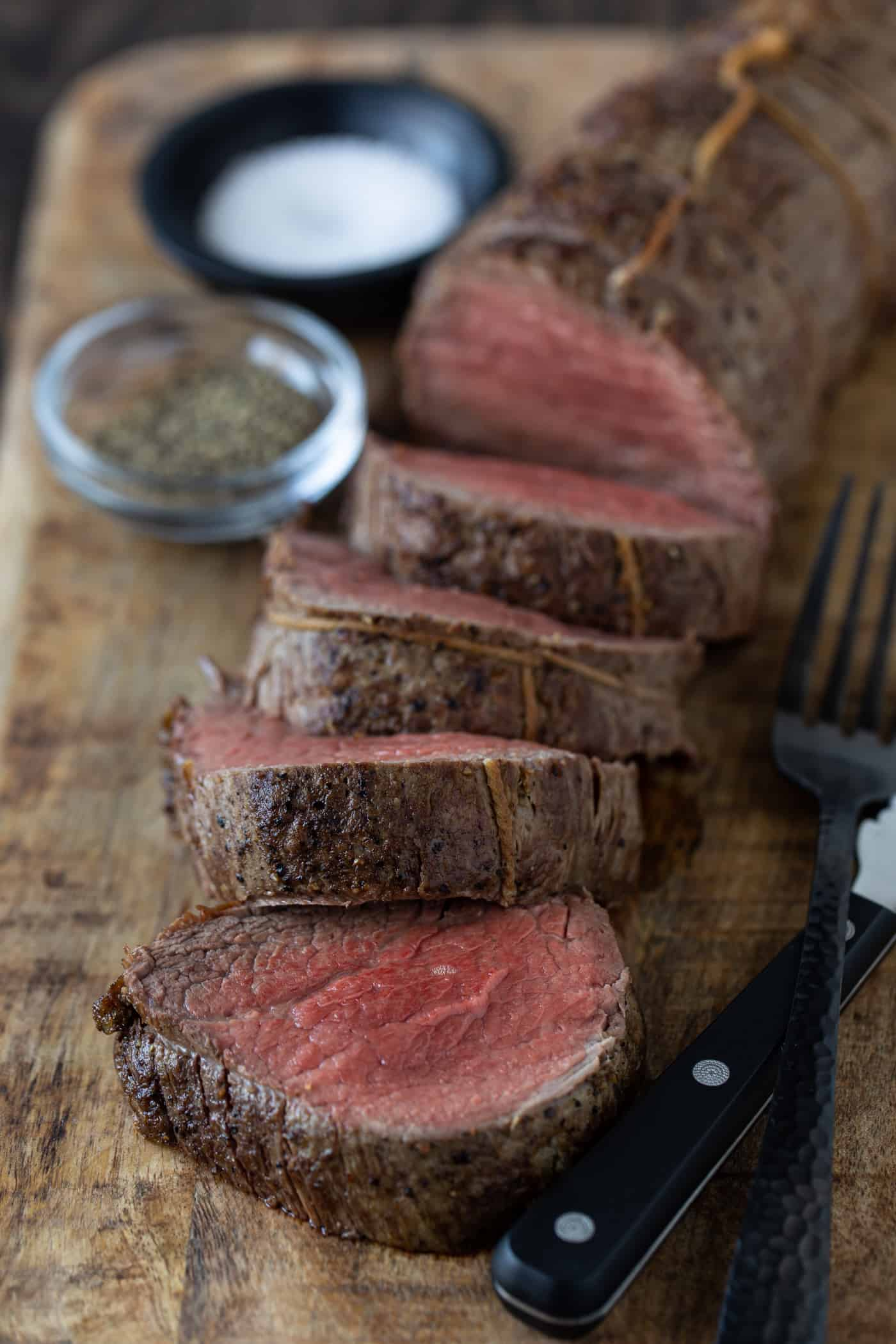 Sliced beef beef tenderloin on cutting board with steak knife and fork.