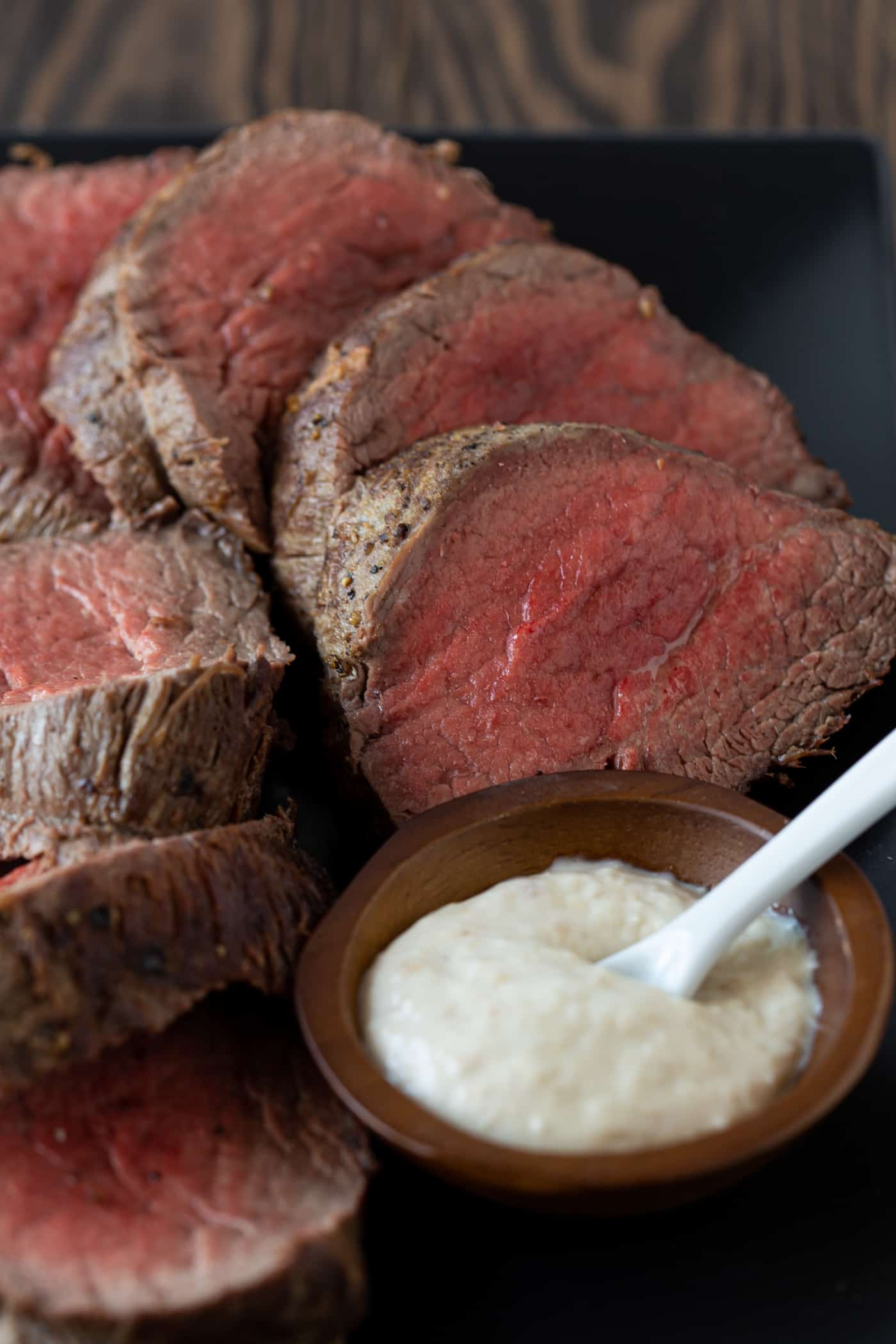 sliced beef tenderloin on platter with horseradish sauce.
