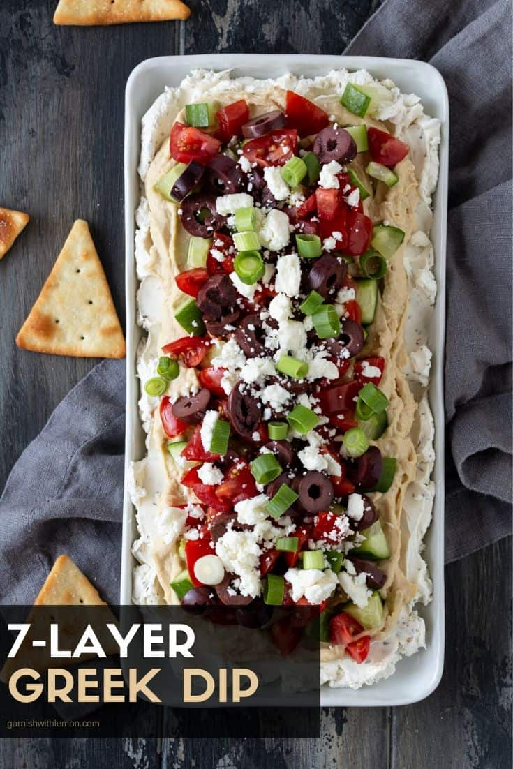 Layered Greek Dip on a white platter. Garnished with pita chips.
