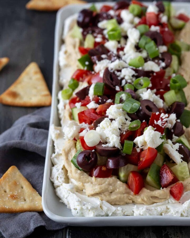 Layered Greek Dip on a white platter surrounded by pita chips.