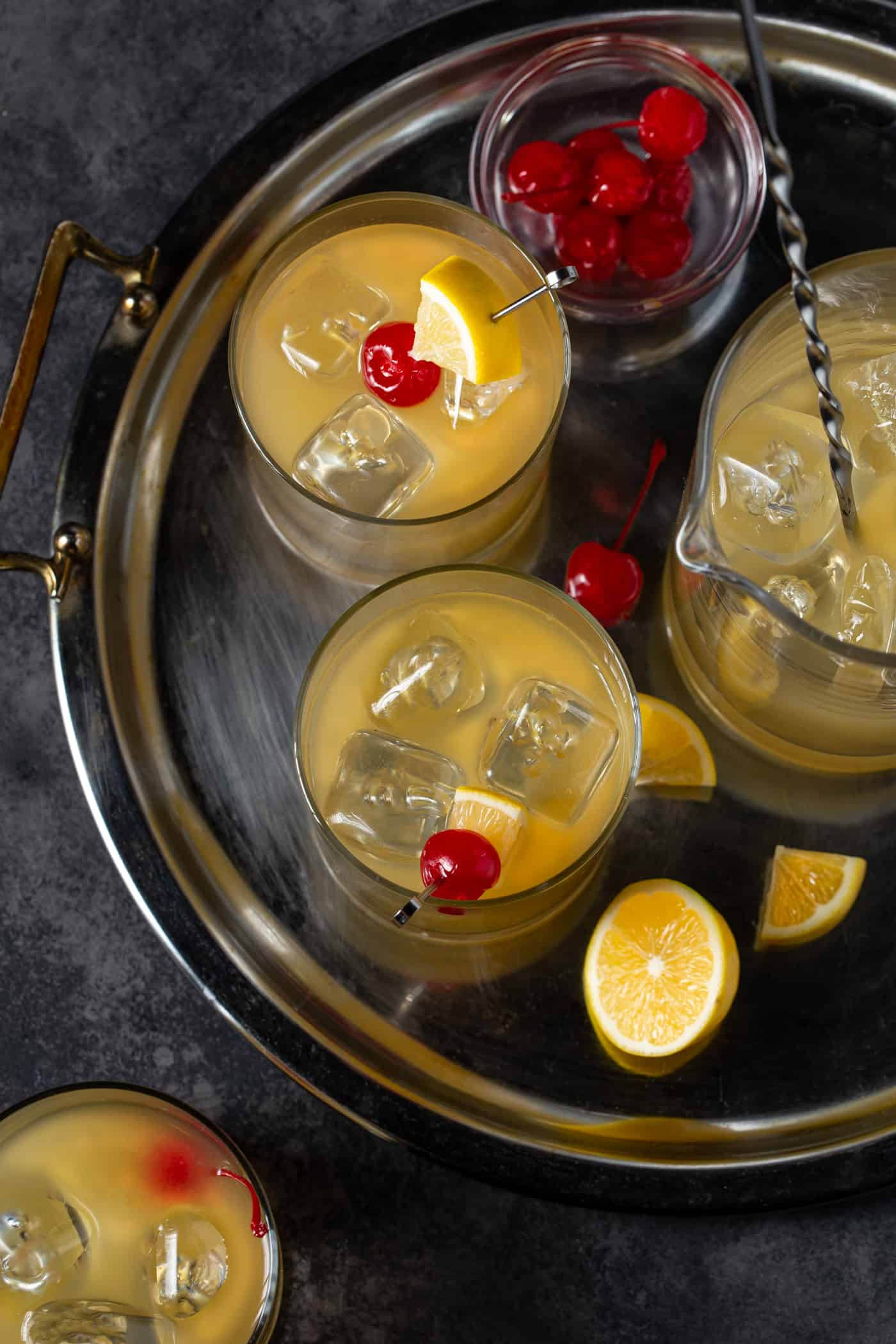 Platter filled with glasses of Whiskey Sours. Garnished with maraschino cherries and Meyer lemon slices.