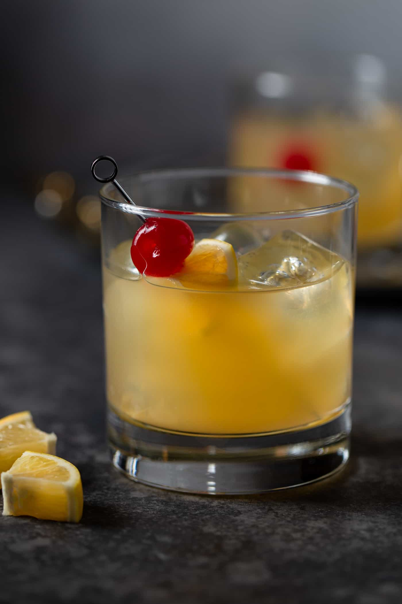 A cocktail in a low ball glass filled with ice and garnished with maraschino cherries and Meyer lemon slices.