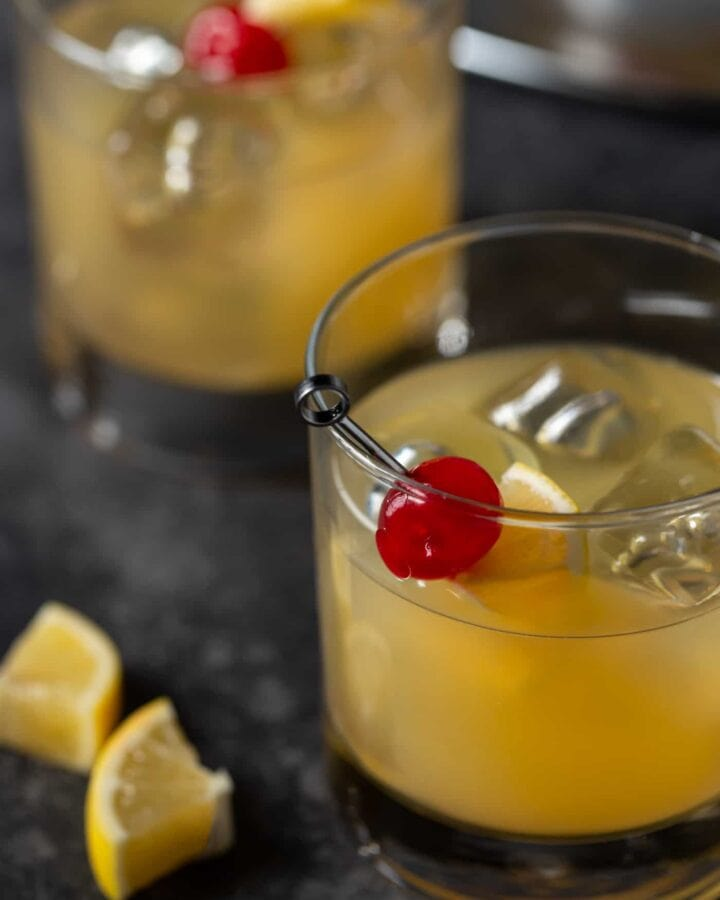 Two lowball glasses filled with Meyer Lemon Whiskey Sour cocktails and garnished with maraschino cherries and meyer lemon slices.