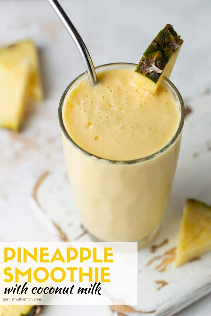 Tall glass of Mango Pineapple Smoothie made with coconut milk. Garnished with a fresh pineapple wedge.