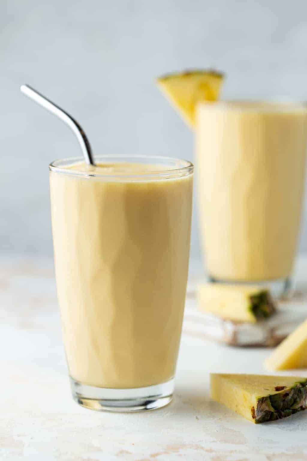 Two tall glasses filled with Mango Pineapple Smoothies and garnished with fresh pineapple wedges.