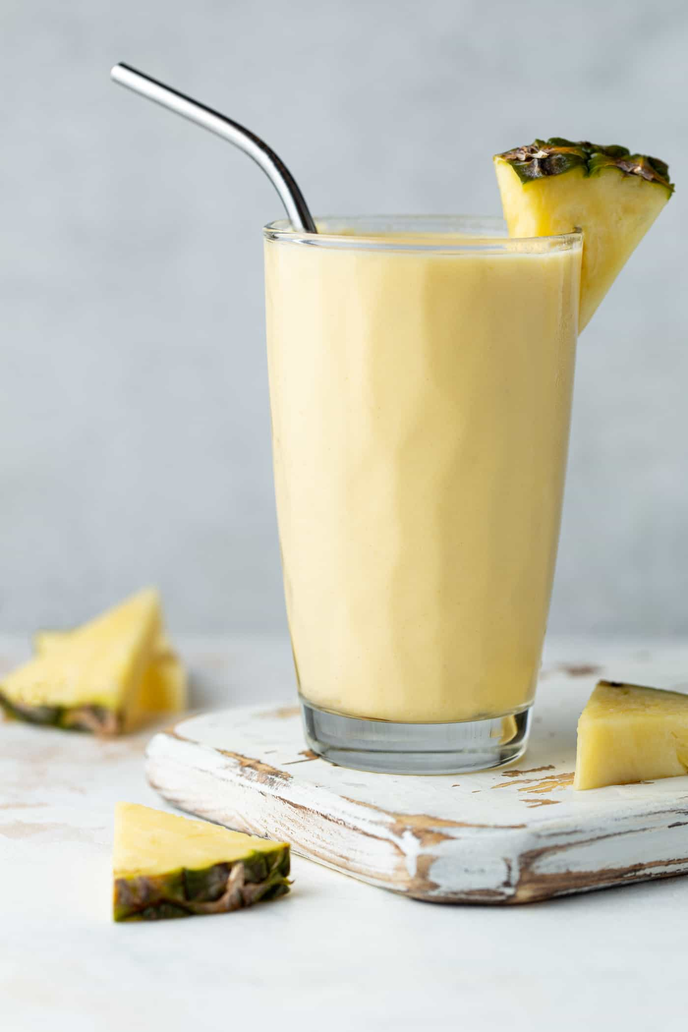 Tall glass of Mango Pineapple Smoothie on a white cutting board. Garnished with a stainless steel straw and a fresh pineapple wedge.