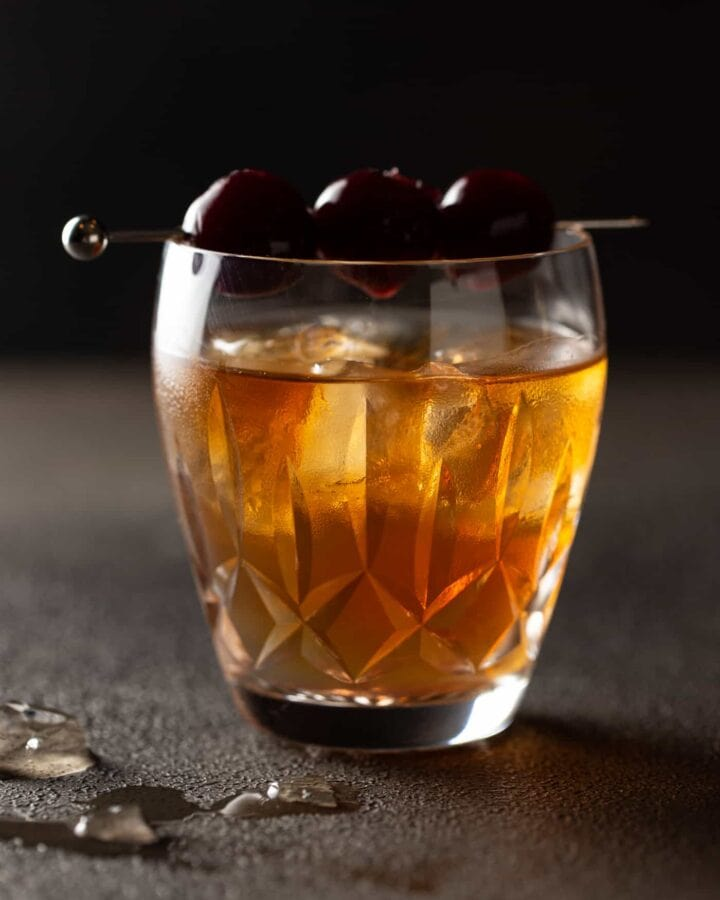Low ball old fashioned glass filled with manhattan cocktail and garnished with a skewer of cherries.