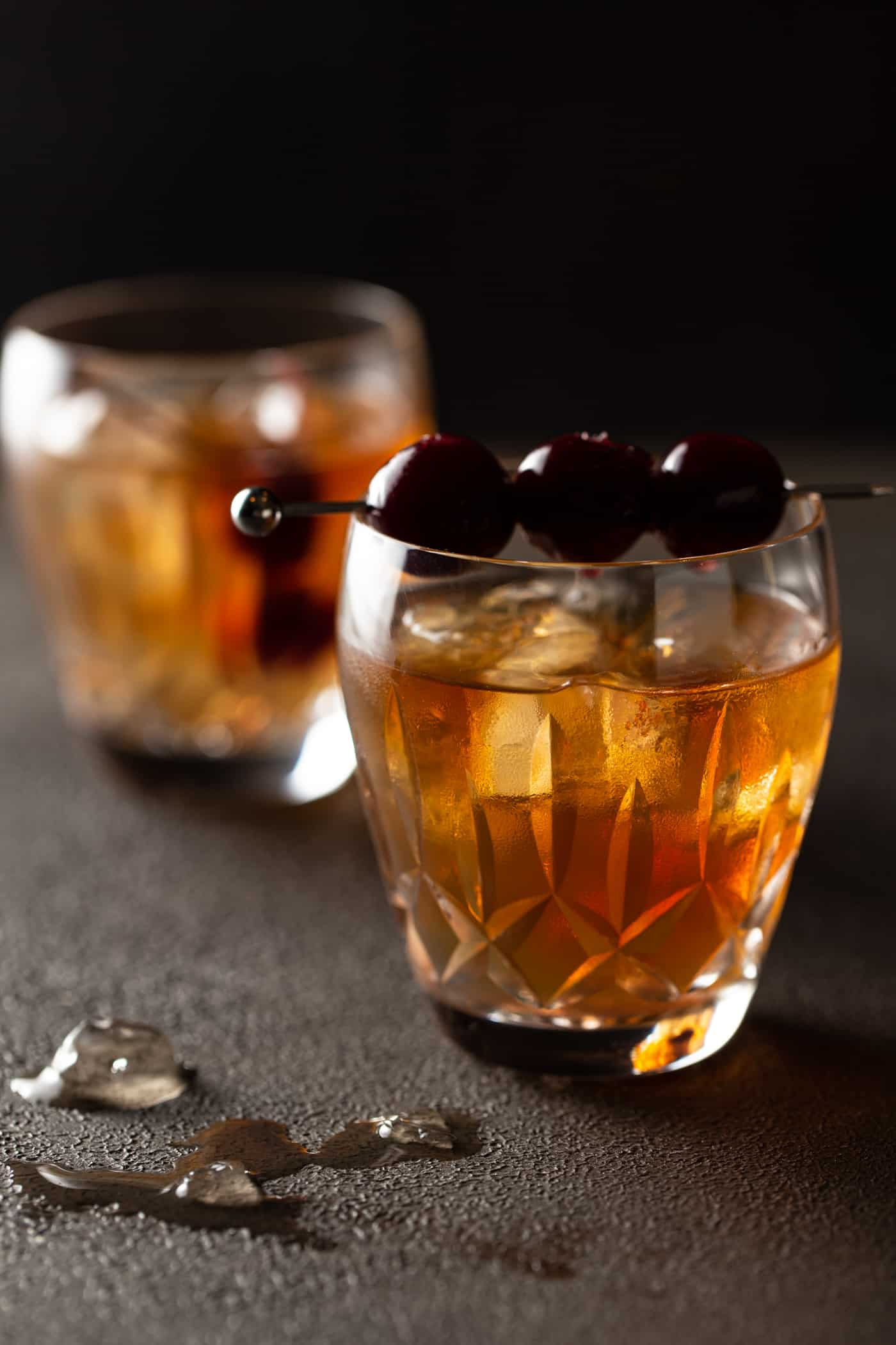 2 crystal glasses filled with ice, bourbon and a skewer of cherries for garnish on a dark background.