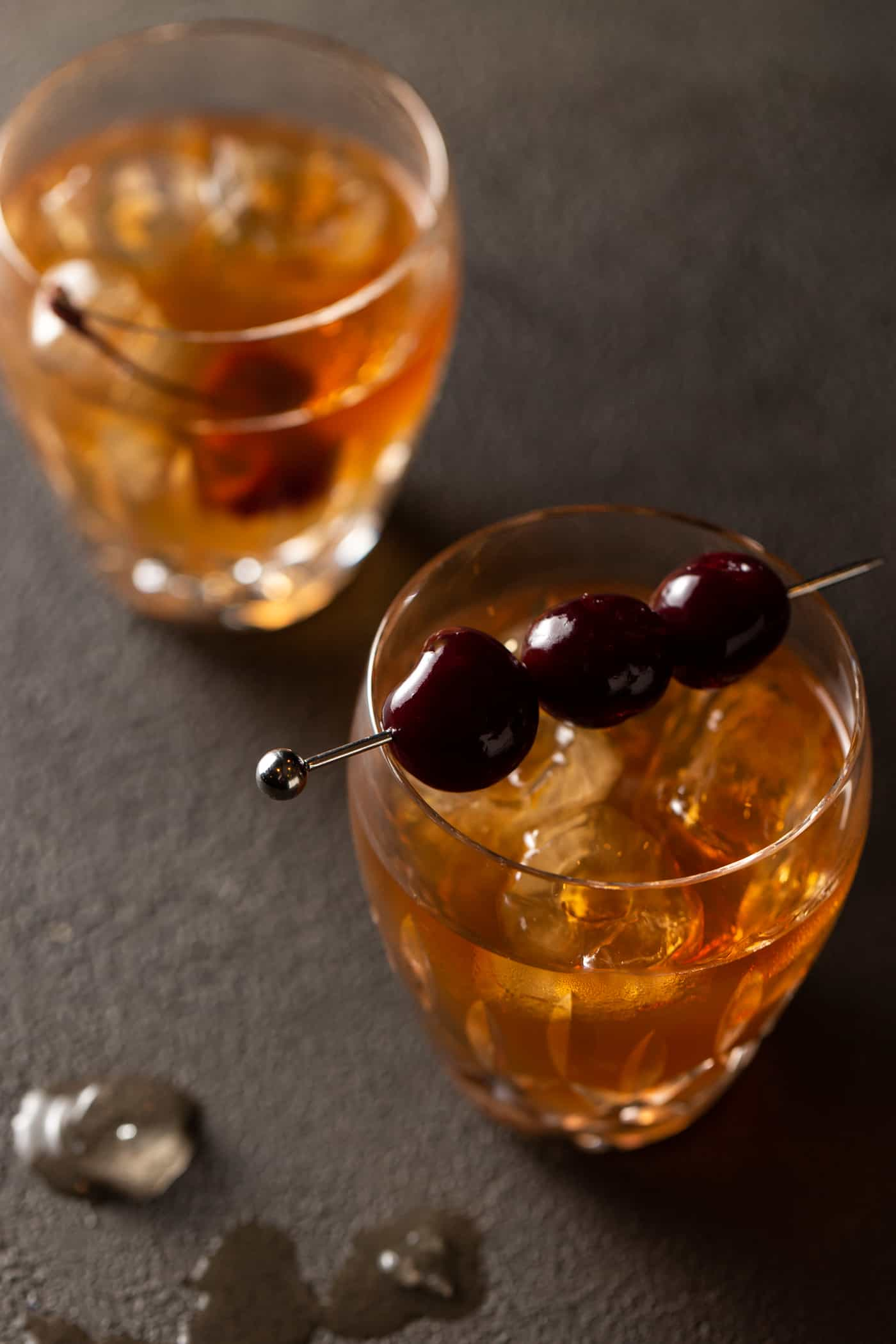 Top down image of classic Manhattan cocktail recipe in 2 old fashioned glasses.