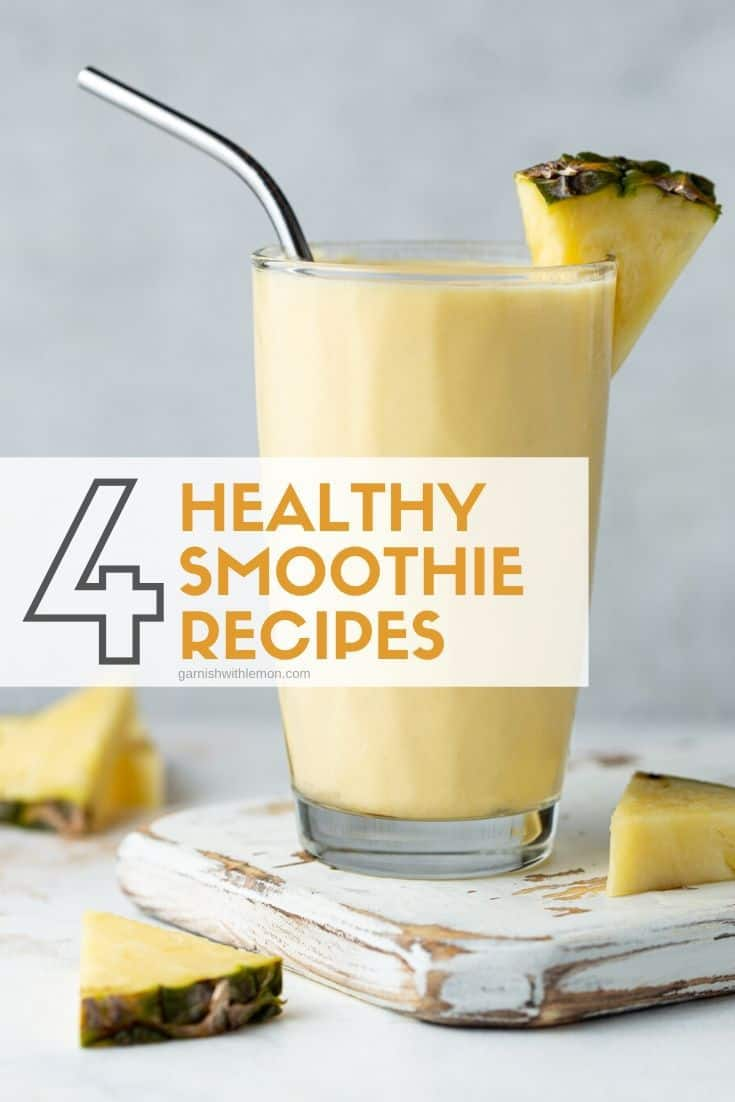 Single glass of pineapple smoothie on a white board. This healthy smoothie is garnished with a stainless steel straw and a fresh pineapple wedge.