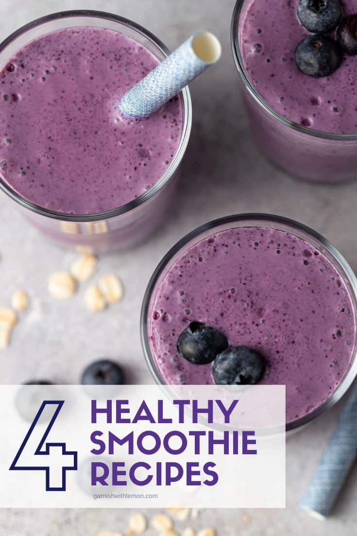 Top down view of healthy smoothies in glasses that are garnished with straws and fresh blueberries.
