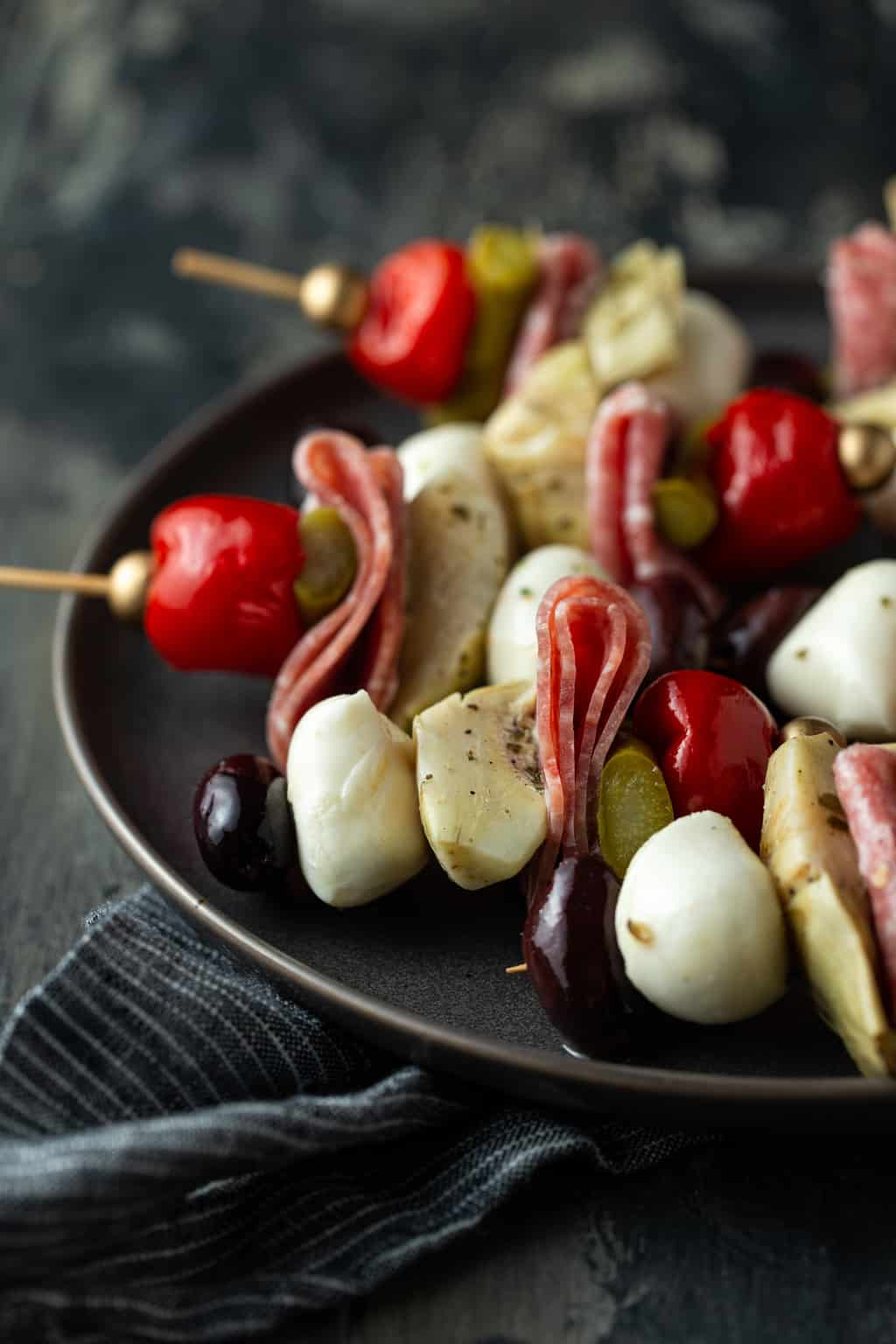 antipasto skewers on plate with gray napkin.