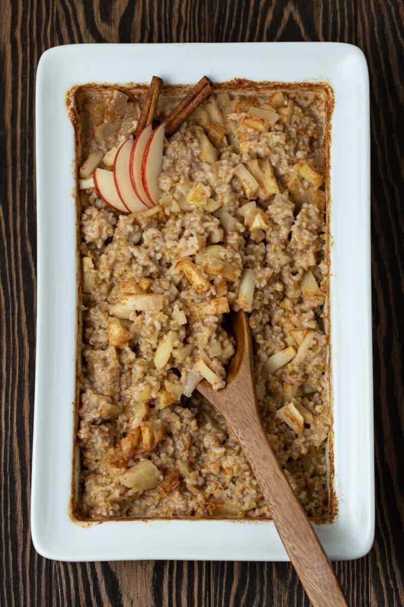 Baked oatmeal with apples and cinnamon in a white baking dish.