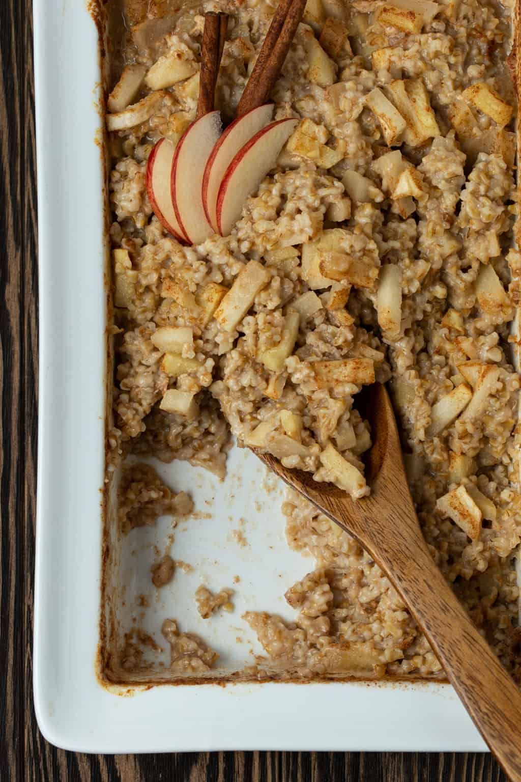 A dish is filled with oatmeal , with Apples and cinnamon.