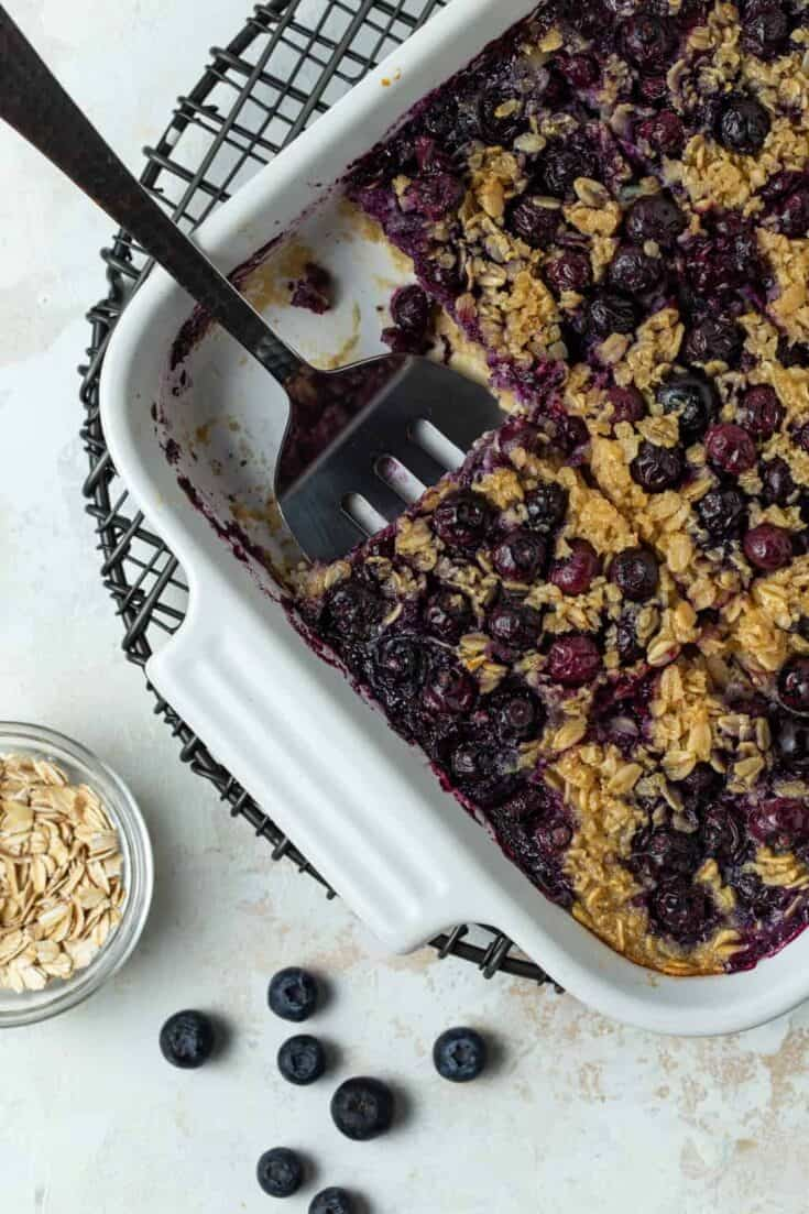Top down image of blueberry baked oatmeal in a white baking dish cut into squares with one piece removed from the pan.