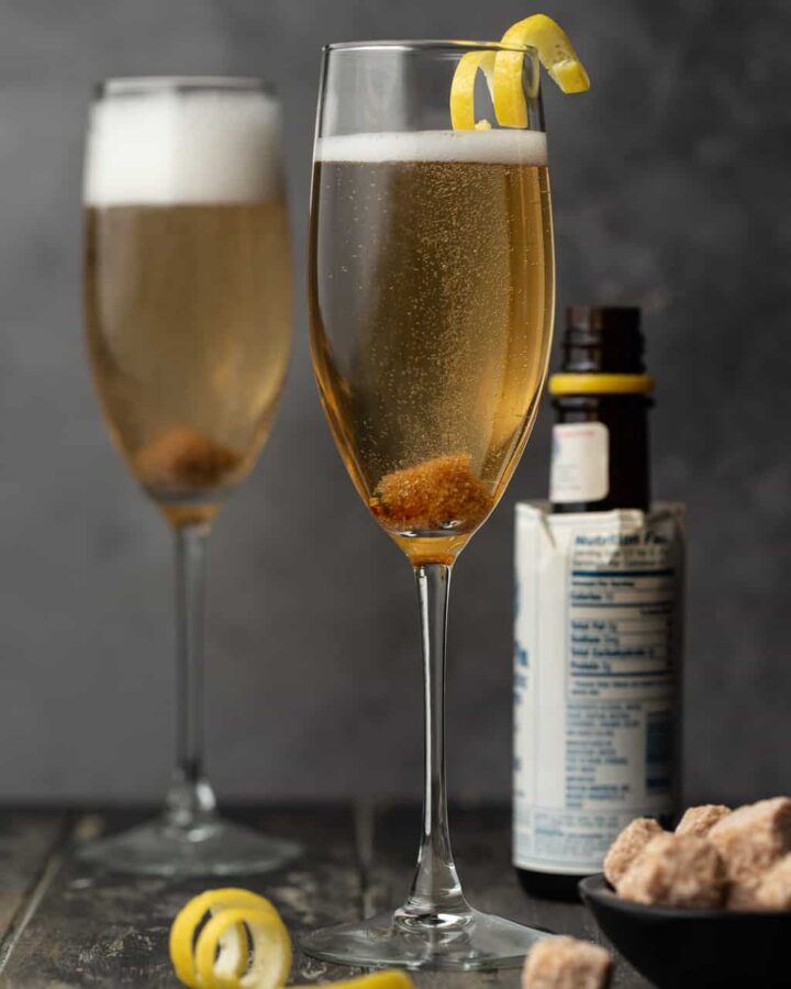 Two flutes filled with Classic Champagne Cocktails and garnished with a lemon twist.