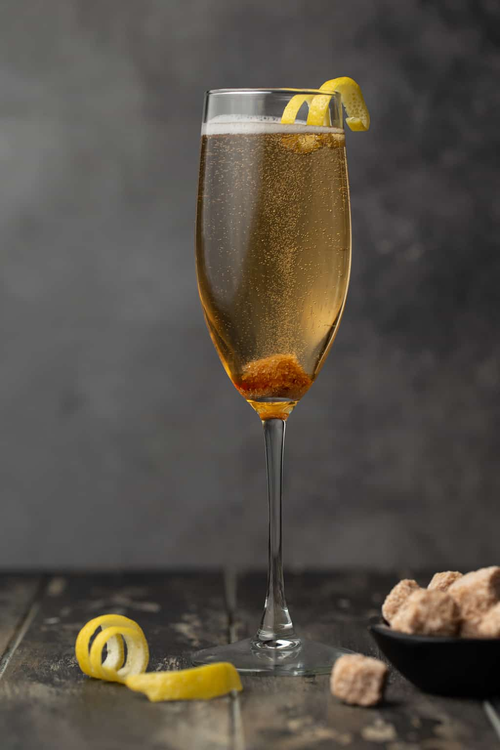 Single champagne flute filled with cocktail and garnished with lemon twist.