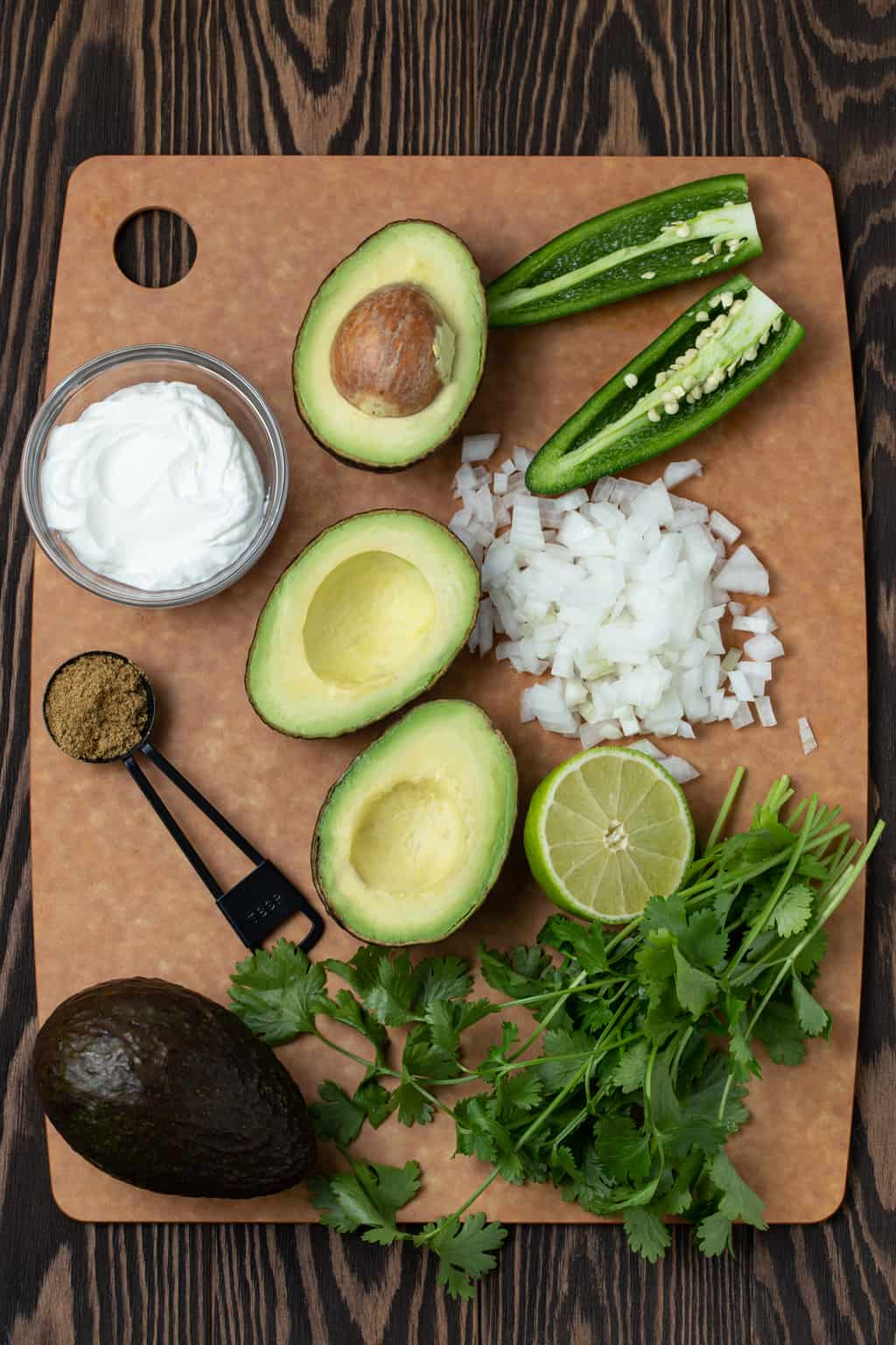 Tan cutting board filled with avocadoes, jalapeno pepper, cilantro, onion and limes to make Healthy Avocado Dip with Greek Yogurt.