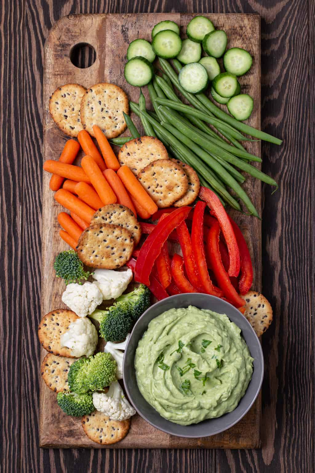 Wooden cutting board filled with vegetables, crackers and a bowl filled with a healthy Avocado Dip that is made with Greek yogurt