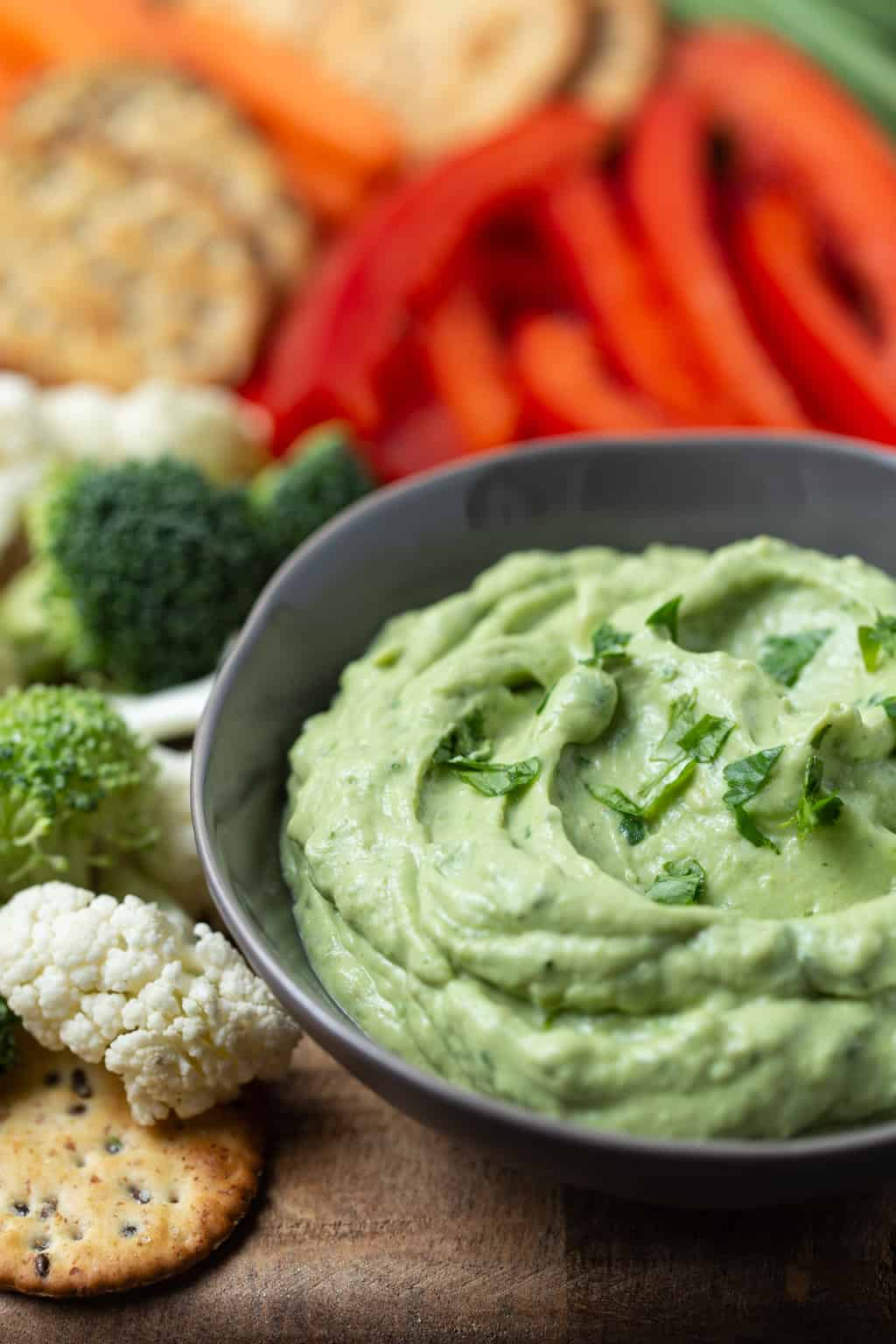 Gray bowl filled with Healthy Avocado Dip made with Greek Yogurt and surrounded by cut veggies for dipping.