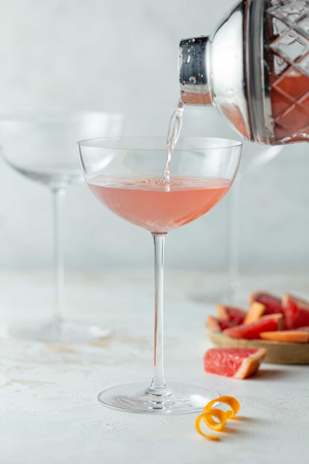 Grapefruit martini being poured into a tall coupe glass with fresh grapefruit wedges on the side.
