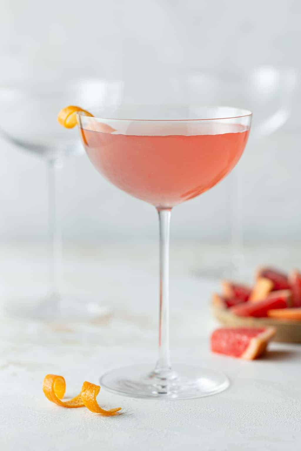 single ruby red grapefruit martini in a tall coupe glass garnished with an orange peel.