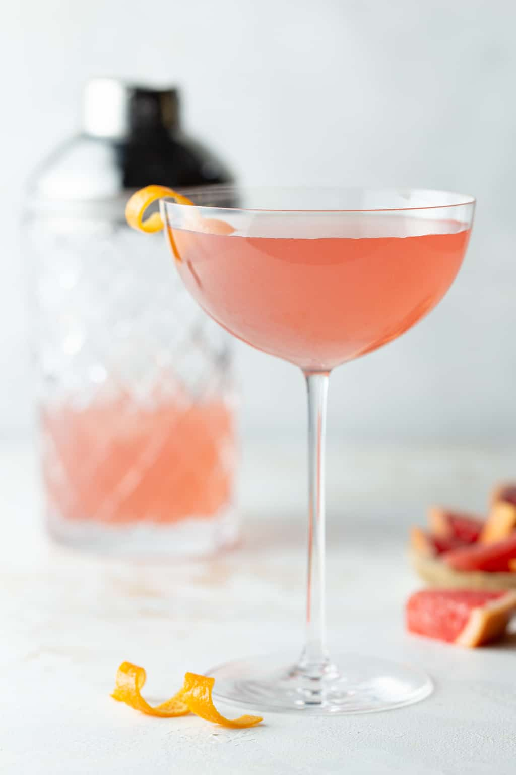 Grapefruit Martini in a tall coupe glass with an empty glass in the background and a pile of grapefruit wedges for garnishes.