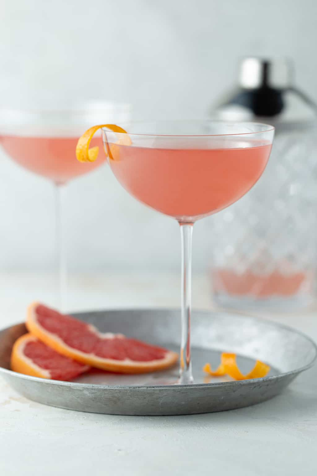 2 pink martinis with a shaker in the background on a white surface.