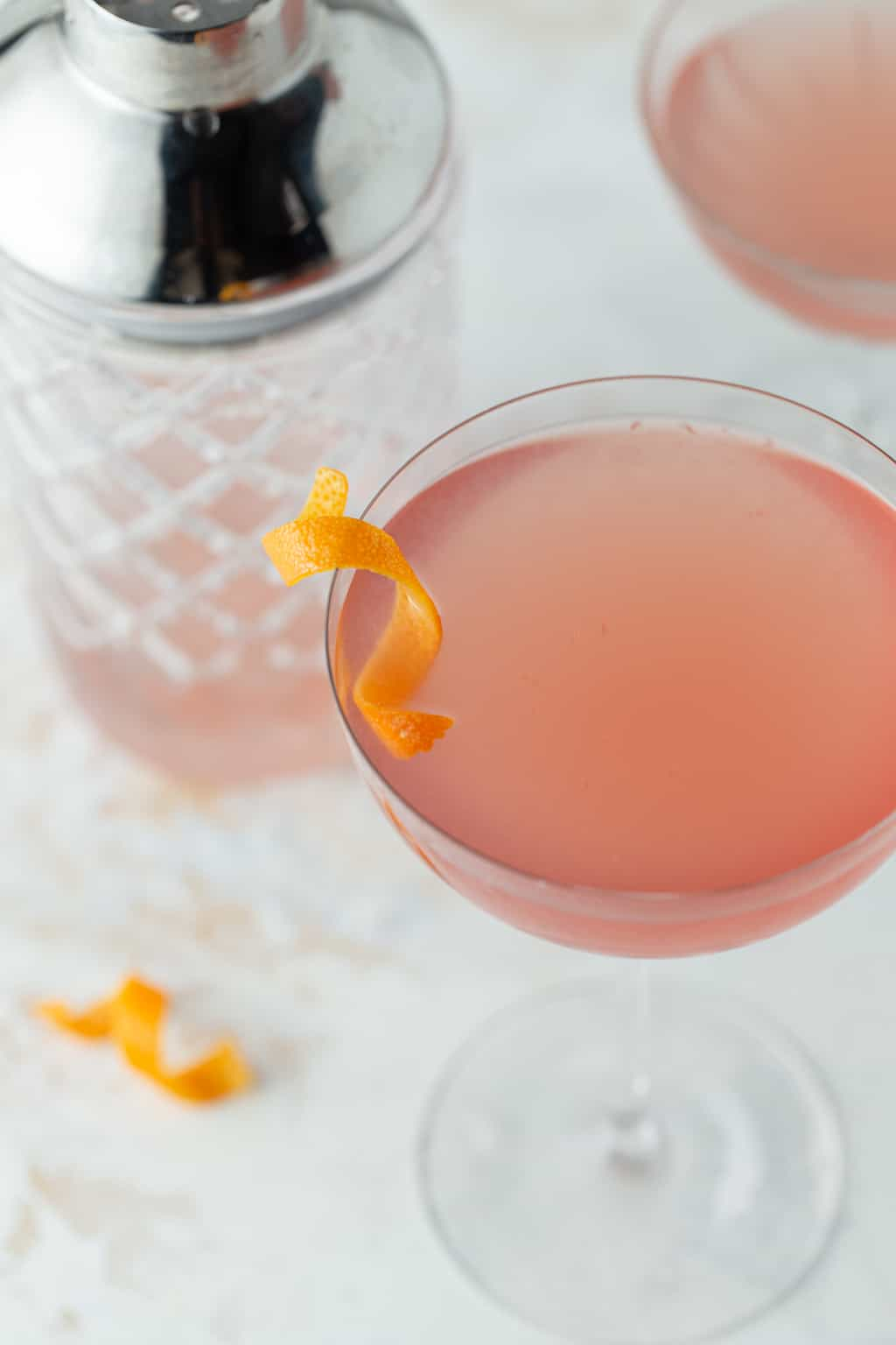 Top down shot of pink grapefruit martini in a tall coupe glass with an orange peel for a garnish.