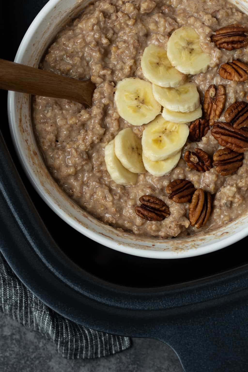 A white bowl filled with Slow Cooker Steel Cut Oats is nestled in a water bath in a slow cooker. Oatmeal is garnished with sliced bananas and pecans.