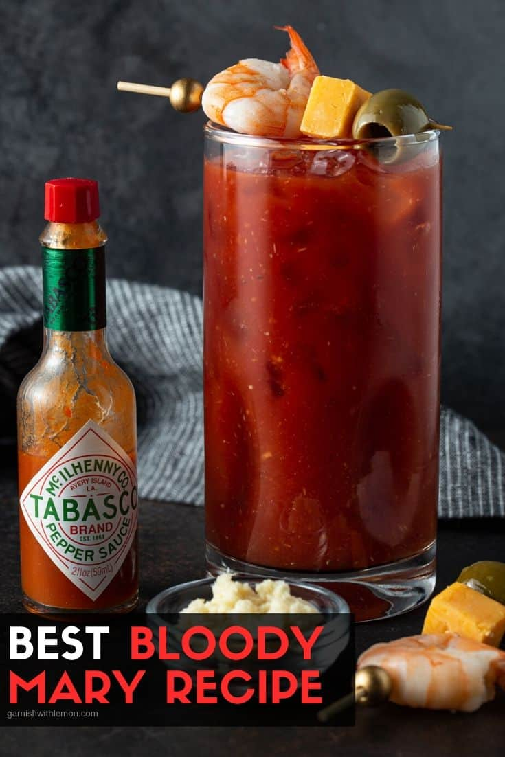 Single Bloody Mary in a high Ball glass with tabasco and fresh horseradish on the side.